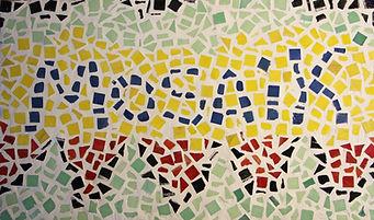 Schriftzug Mosaik, welcher aus Mosaiksteinen zusammengesetzt ist.