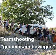 Foto von unserem Team, welches einen 2CV einen Hang hinaufschiebt und zieht.