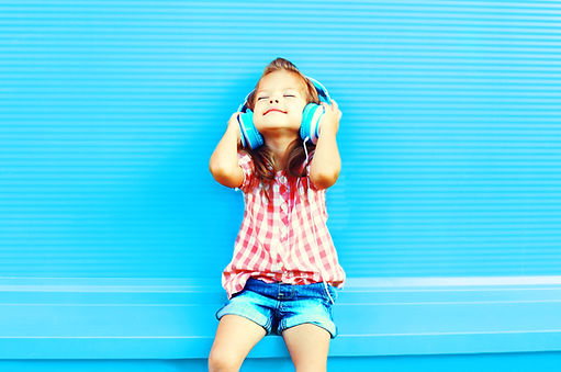 Happy little girl child listens to music