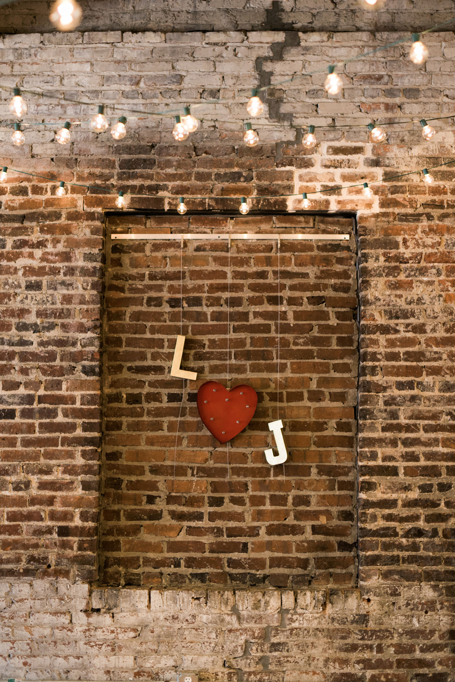 l heart j initials on brick wall