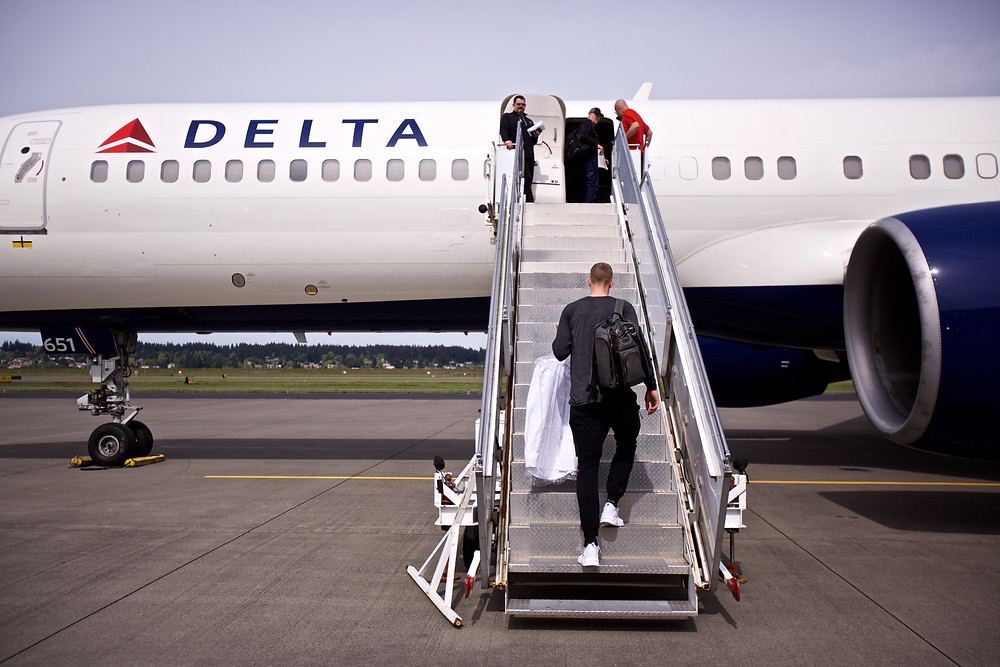 NBA Player Mason Plumlee of the Denver Nuggets carrying clothes onto the team airplane