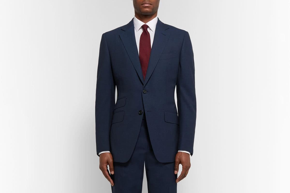 Black man wearing navy suit and wine tie