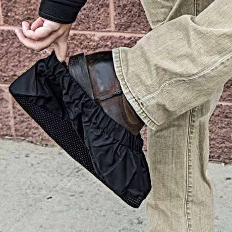 man slipping on boot covers before entering house