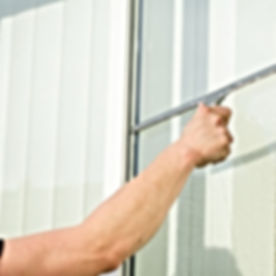Man Cleaning Window With Squeegee