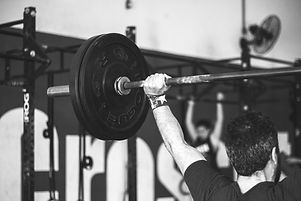 man%20carrying%20barbell%20at%20the%20gy