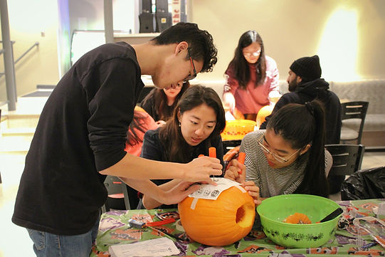 Students carving a pumpkin at an OSL event