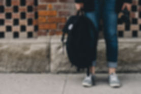 Student holding backpack in hand