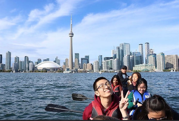 Students sitting on a kayak, posing in front of the toronto harborfront