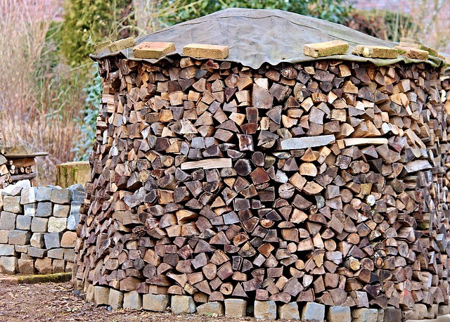 A circular log pile with a rock pile beside it