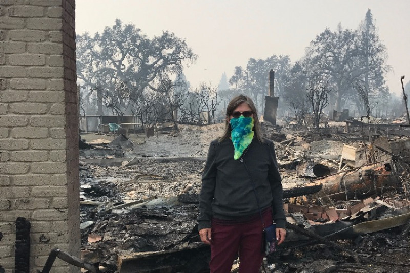 Melinda Bachman in front of her burned home