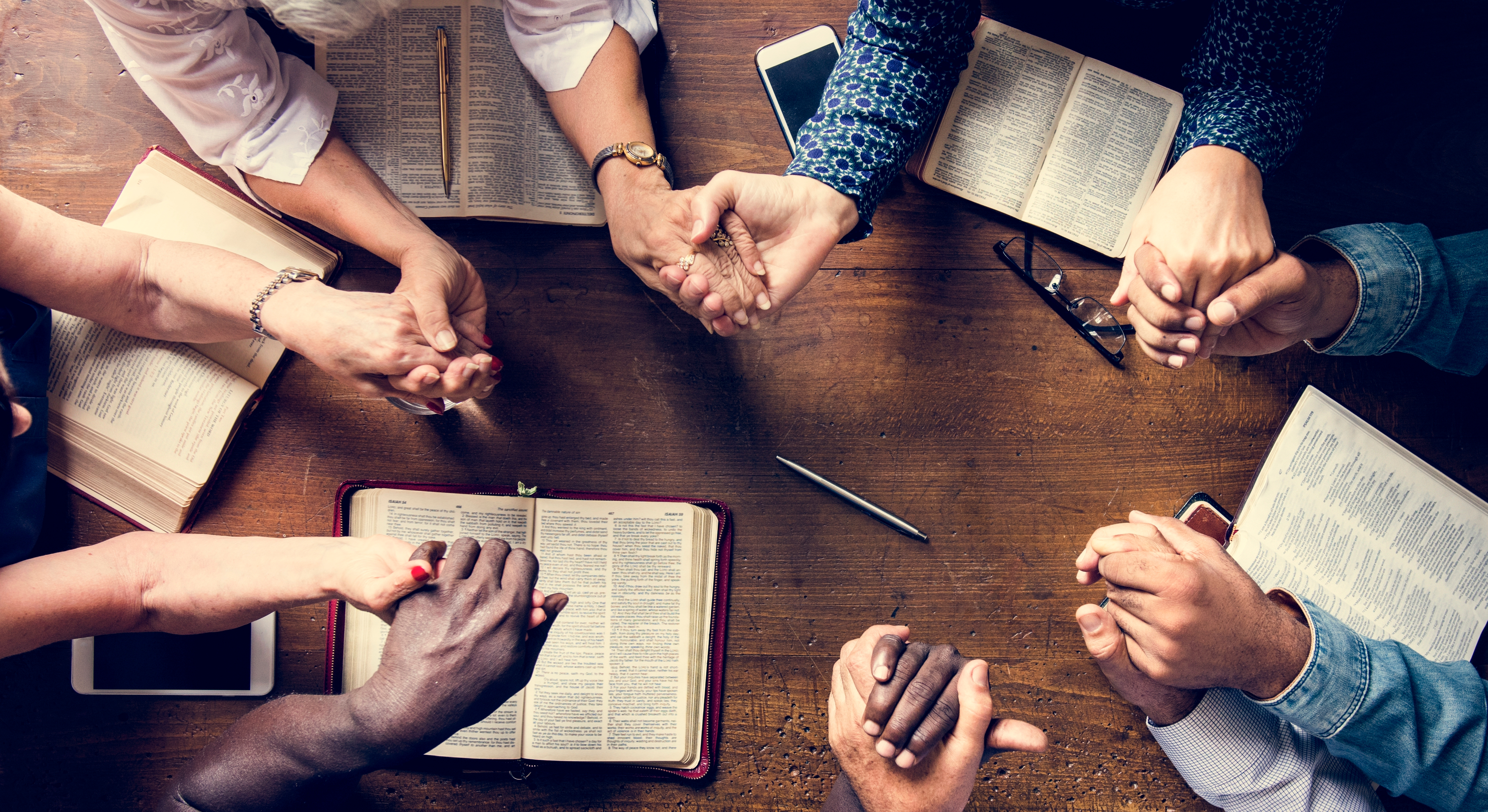 Group of people holding hands praying worship believe.jpg