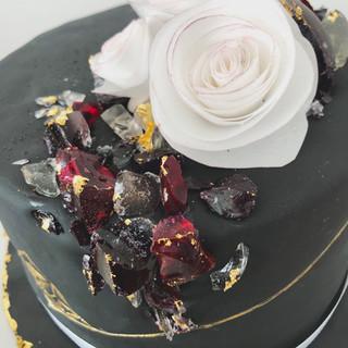 Black Birthday Cake mit Zuckerkristallen und handgemachten Blüten