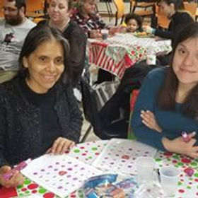 A mother and daughter sitting at a table smiling