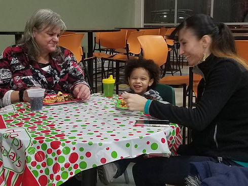 Two ladies and a little boy sitting at a dinner table, laughing.