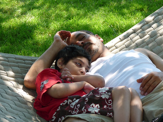 Father and son resting on a hammock.