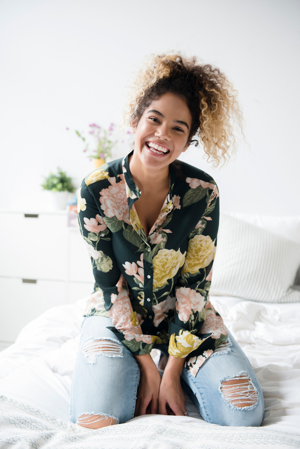 Girl, sitting on the bed smiling.