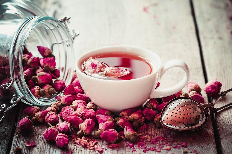 Rose buds tea, tea cup, strainer and gla