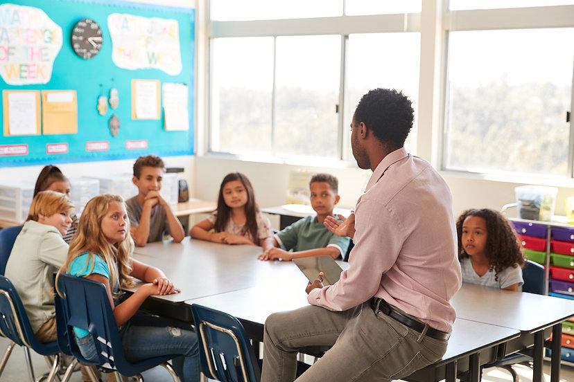 male-teacher-with-elementary-school-kids