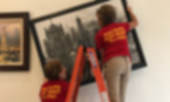 Goldilocks Solutions team Hanging client artwork