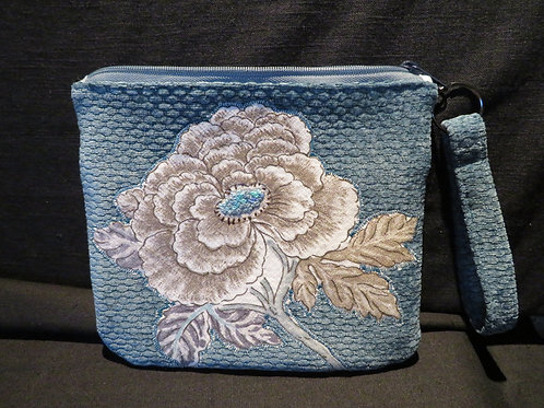 Brown and cream embroidered floral pattern on teal blue quilted fabric