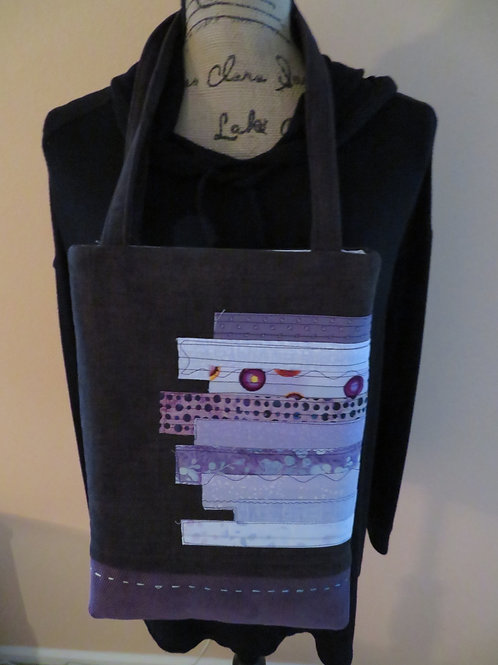 Funky shaped purse with horizontal swatches of patterned cloth