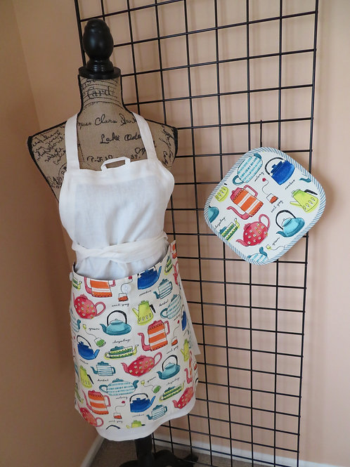 Adult White linen apron with colorful tea pots on towel and pot holder