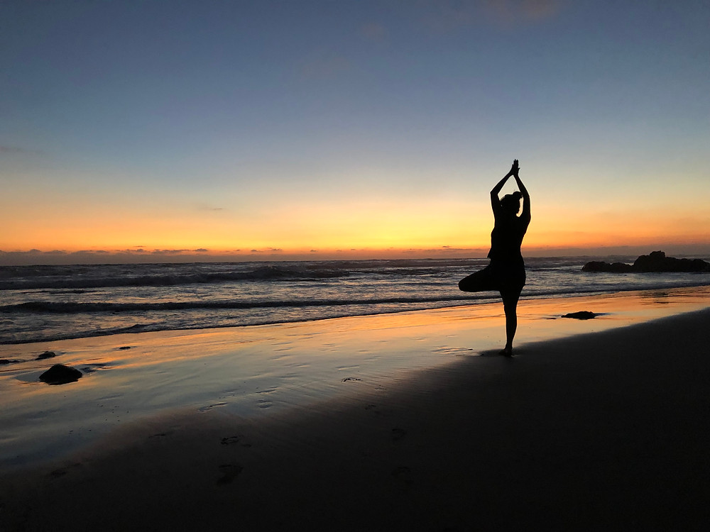 Woman doing a yoga pose on the beach while watching the sunset