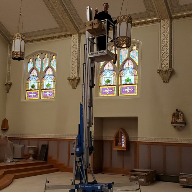 Fr. Tim changing light bulbs