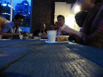 Eating prasad with our event guests on a rooftop dining table
