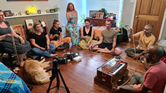 Guests learning how to chant on meditation beads at a home program near Singleton.