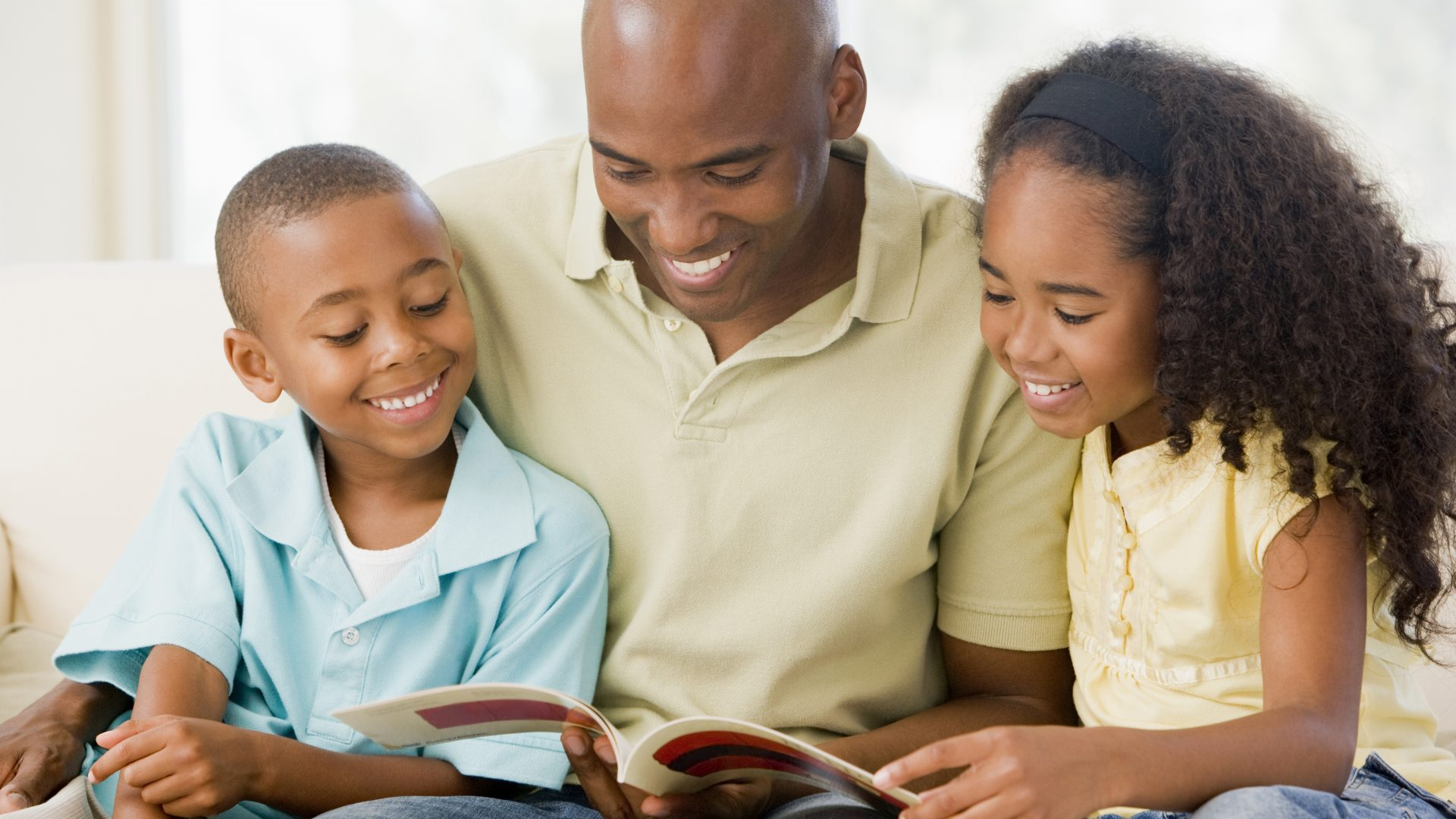 cropped-man-and-two-children-sitting-in-living-room-reading-book-and-smiling_SFQvbsArs-1