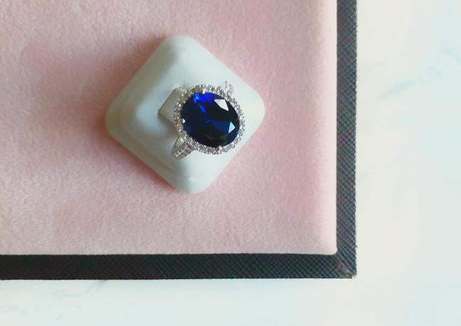 Anello inoro bianco 18K con zaffiro centrale e diamanti.