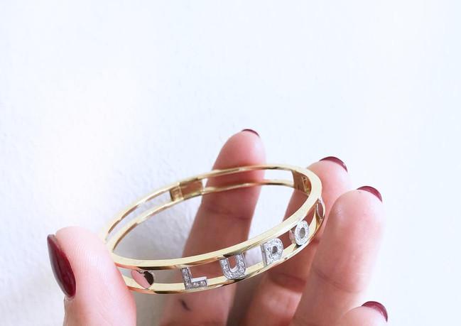 Braccialetto rigido in oro giallo e lettere in oro bianco e diamanti.