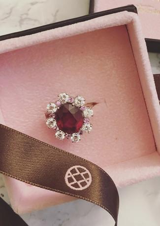 Anello in oro bianco rubino centrale, zaffiri rosa e diamanti.