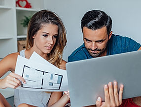 Couple at home reviewing building plans on a laptop and on paper