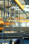 metaldele på transportbånd på vej til overfladebehandling