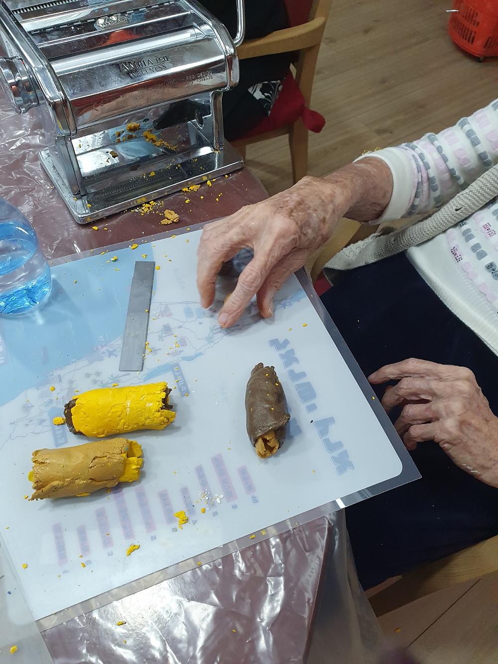 קשישה יוצרת גלילי פימו  במכונת הפסטה