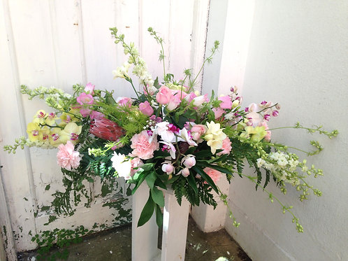 Orchid and larkspur funeral spray