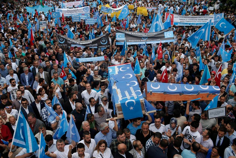 n this July 2015 photo, Uighurs living in Turkey and their supporters, some carrying coffins representing Uighurs who died in China's far-western Xinjiang Uighur region, chant slogans as they stage a protest in Istanbul, against what they call oppression by the Chinese government against Muslim Uighurs in the province