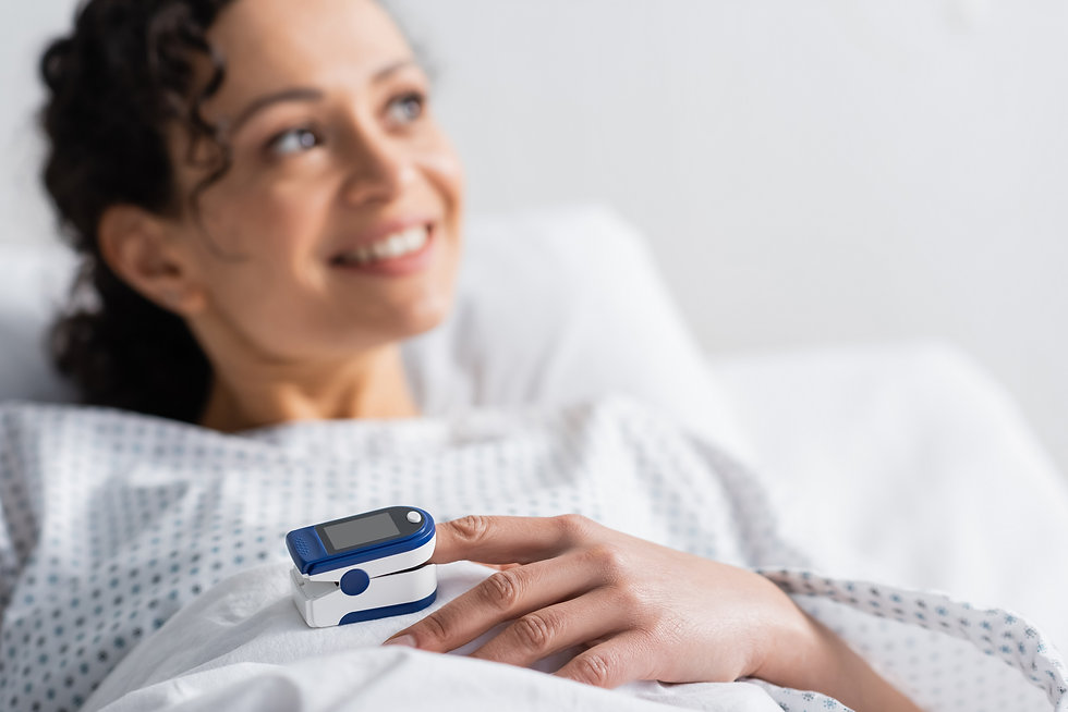 smiling african american woman with pulse oximeter on finger looking away in hospital, blu