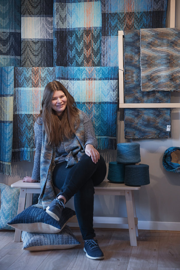 A photo of Lucy sitting on a bench in front of a selection of her handwoven throws and scarves