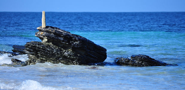 A black rock sticking up from the bright blue sea