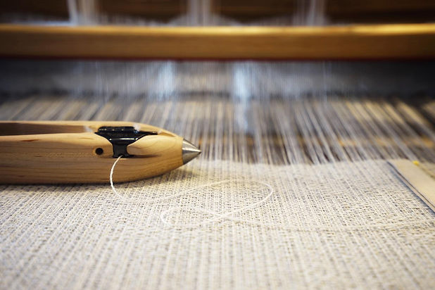 A weaving shuttle on a pale coloured woven fabric with a thread twisting to the side