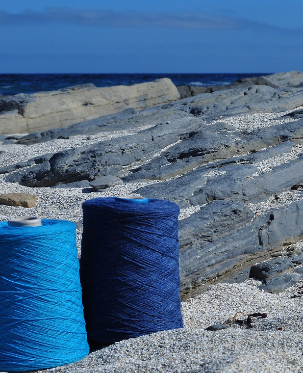 Two cones of blue wool, one lighter than the other, sitting on a sandy beach with grey rocks behind