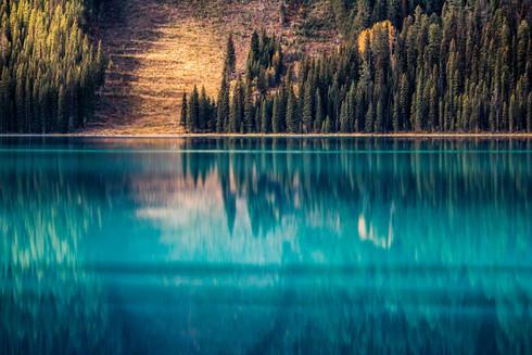 Aqua blue lake reflecting hillside and evergreen trees