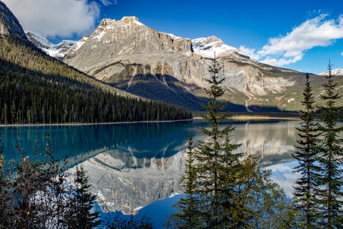Reflections of a rocky peak into a turquoise lake