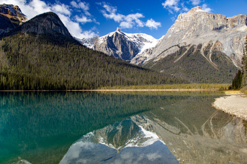 Rocky mountain peaks reflected in a bright turquoise lake