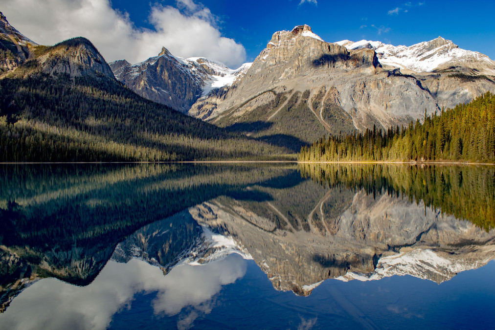 Mountains and tree covered hills reflecting in a mountain lake