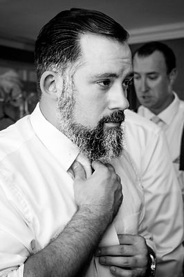 A groomsman checking his tie while getting ready for a wedding
