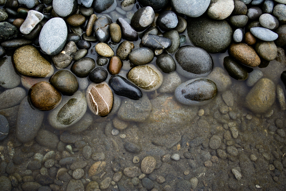 Rounded stream rocks with water in the forground
